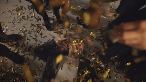 Dropping Confetti On A Man Lying Down On The Floor