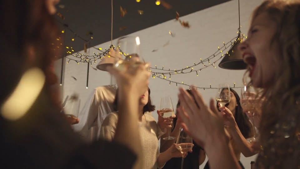People In A Party Raising Their Glasses For A Toss While Confetti Are Falling