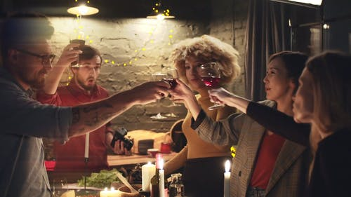 A Group Of People Tosses Their Glasses Of Wine In Unison