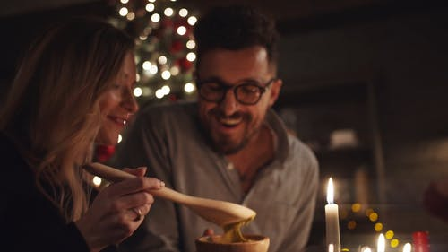 A Woman Jokingly Let A Man Taste The Dipping Using A Large Wooden Spoon