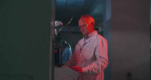 A Man Of Science Observing A Liquid Sample Inside A test Tube