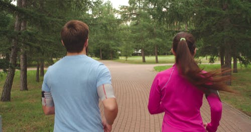 Backside Of A Man And Woman Jogging In A Park