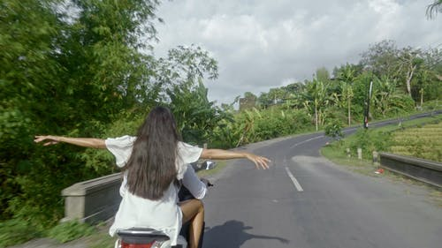 A Couple Riding A Motorcycle In A Road Trip To The Countryside