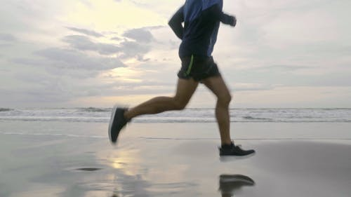 A Man Running In The Beach Shoreline