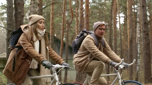 Two People Having A Conversation While Riding In Bicycles In The Woods