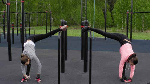 Two Women Doing Bending And Stretching Exercises