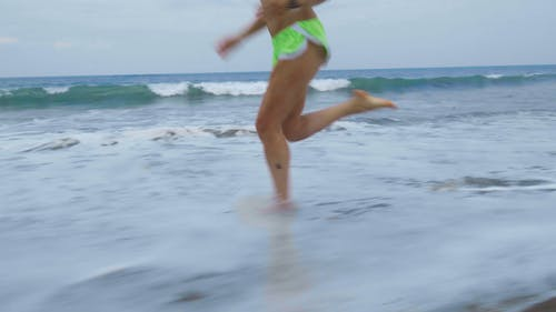 A Woman Running Barefooted On A Beach Shoreline
