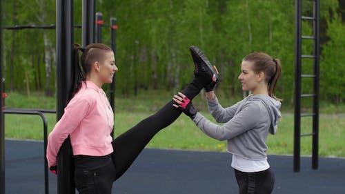 Kobieta Pomaga Innej Kobiecie Podnieść Nogę Do Pełnego Rozciągnięcia
