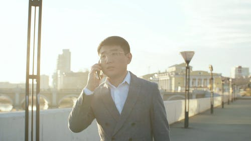 A Man Talking On His Cellphone While Walking