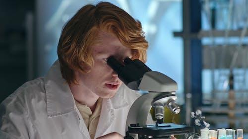 Frau, Die Durch Ein Mikroskop Schaut