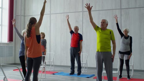 Am Instructor Showing A Group Of Elderly People Some Bending Exercise