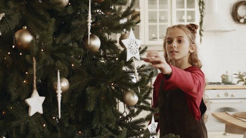 A Girl Busy Arranging The Ornament Decors Hanging In A Christmas Tree