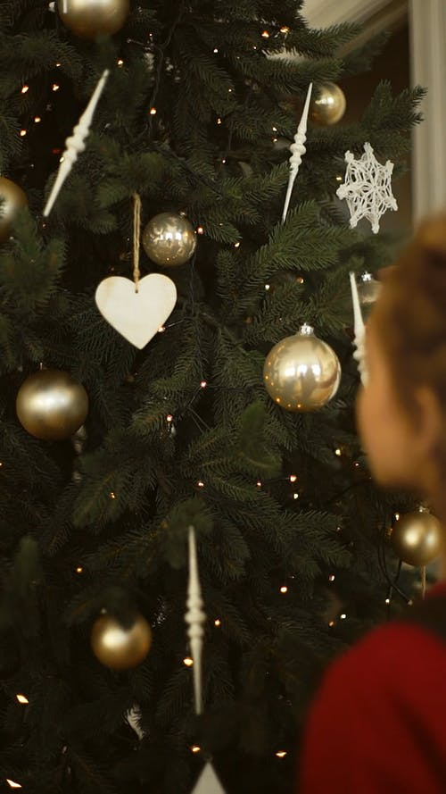 A Girl Arranges The Ornaments Hanging In The Christmas Tree