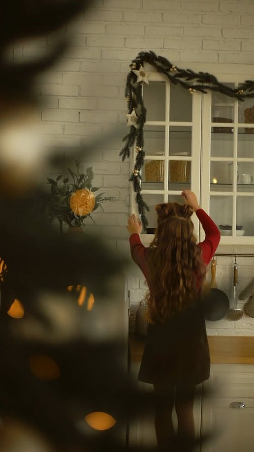 A Girl Arranges A Christmas Garland Hanging By The Kitchen Cabinet