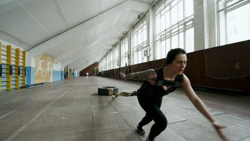 A Woman Doing Extreme Exercise, By Pulling A Tied Tire Attached To Her Body