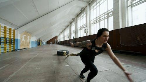 Kobieta Wykonująca Ekstremalne ćwiczenia, Ciągnąc Zawiązaną Oponę Przyczepioną Do Jej Ciała