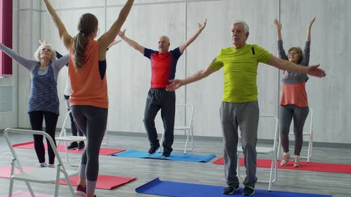 A Woman Fitness Instructor Teaching The Group Of Elderly People Some Exercises Fitted For Them