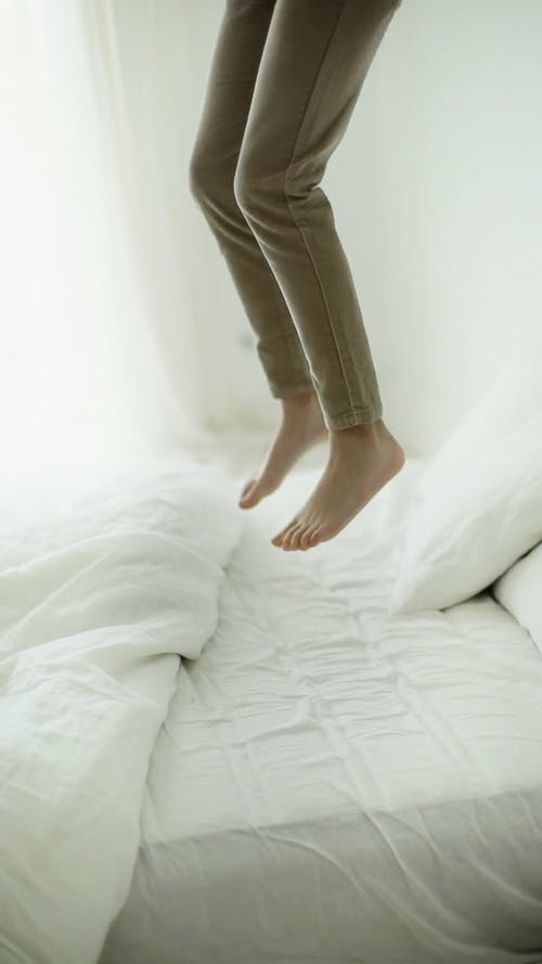 A Person Jumping Up And Down On A Bed