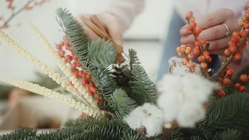 A Person Making A Vase Of Christmas Ornaments Arrangement