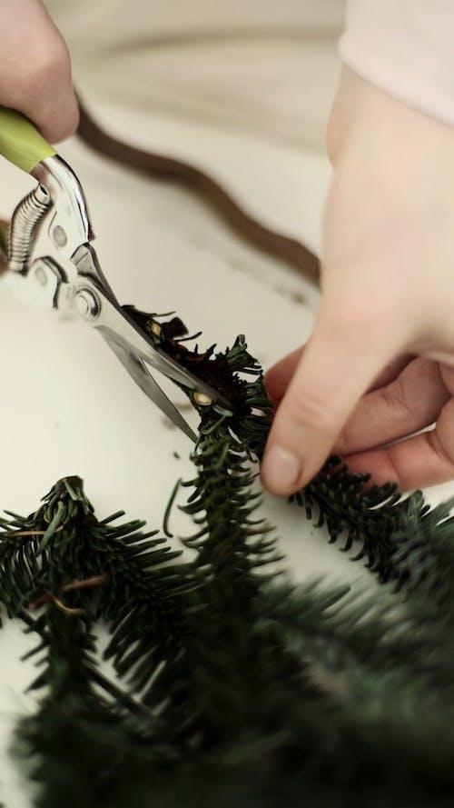 A Person Cutting The Christmas Garland Using A Scissor