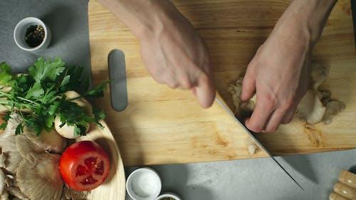 A Person Slicing Mushrooms