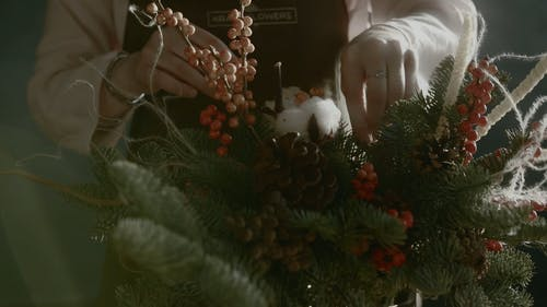 A Person Arranging The Christmas Ornaments Decor Used For A Vase