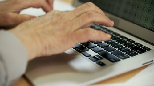 Person Typing Slowly On A Laptop