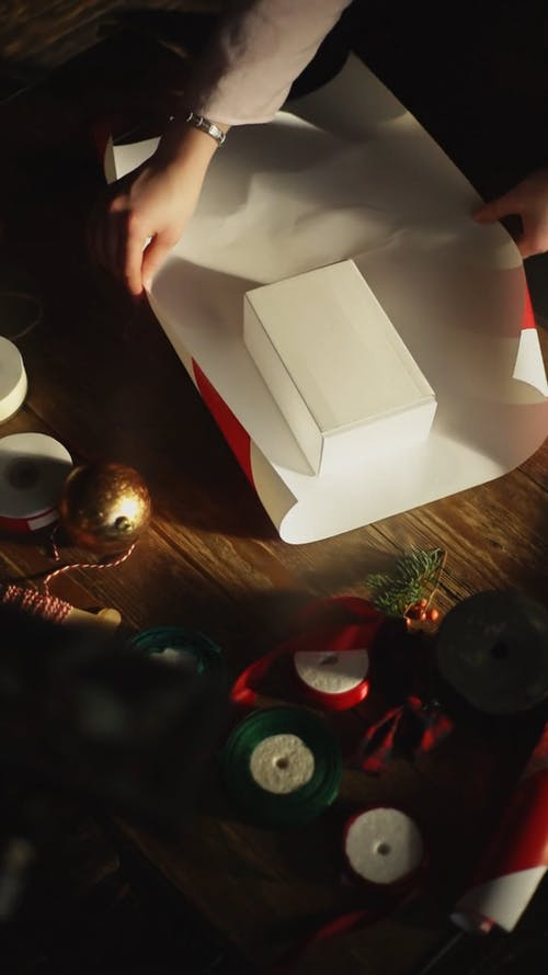 A Person Cuts A Gift Wrapper To Cover The Box Of Gift