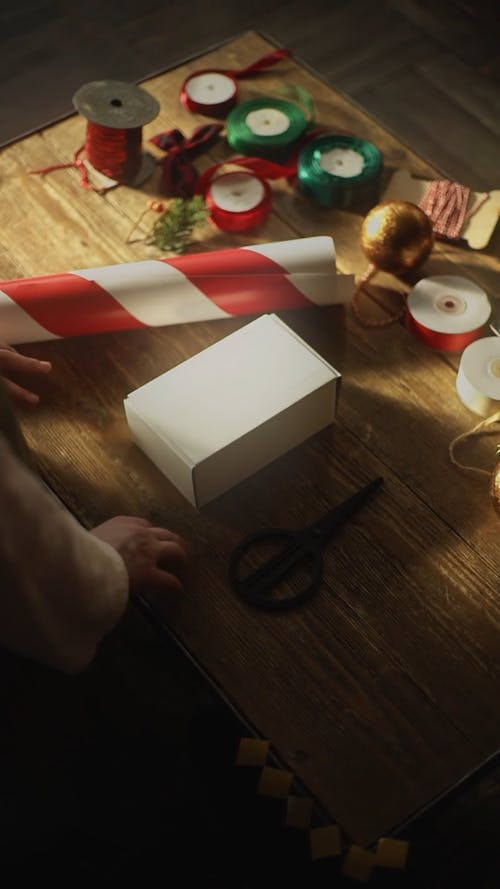 A Person Preparing To Gift Wrap A Box Of Gift