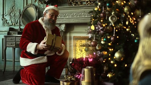 Santa Claus Sneaking To Place A Box Of Gift Under A Christmas Tree