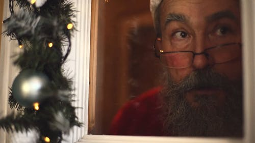 An Elderly Man Dressed As Santa Clause Peeking Through The Curtain From Inside A House