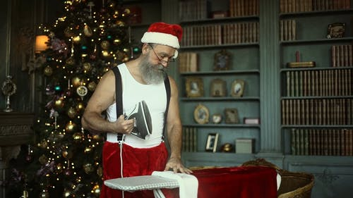 A Man In Santa Claus Costume Ironing His Clothes
