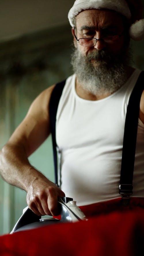 An Elderly Man Ironing His Santa Claus Costume