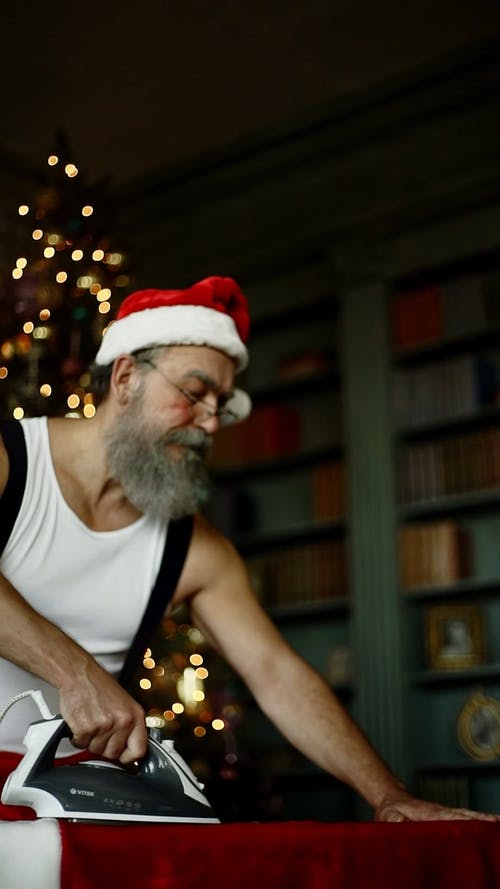 Man In A Santa Claus Costume Wondering While Ironing