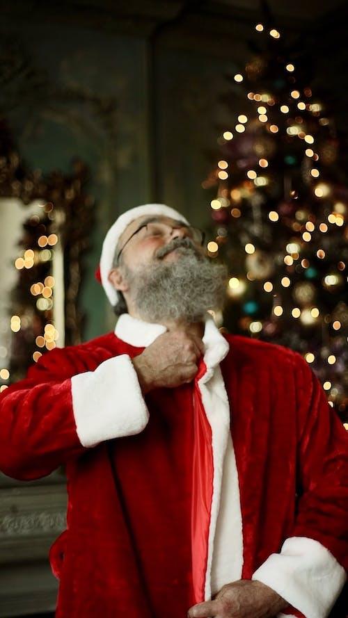 An Elderly Man Zipping Up His Santa Claus Costume