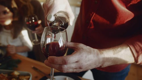 A Person Poring Red Wine On A Wineglass