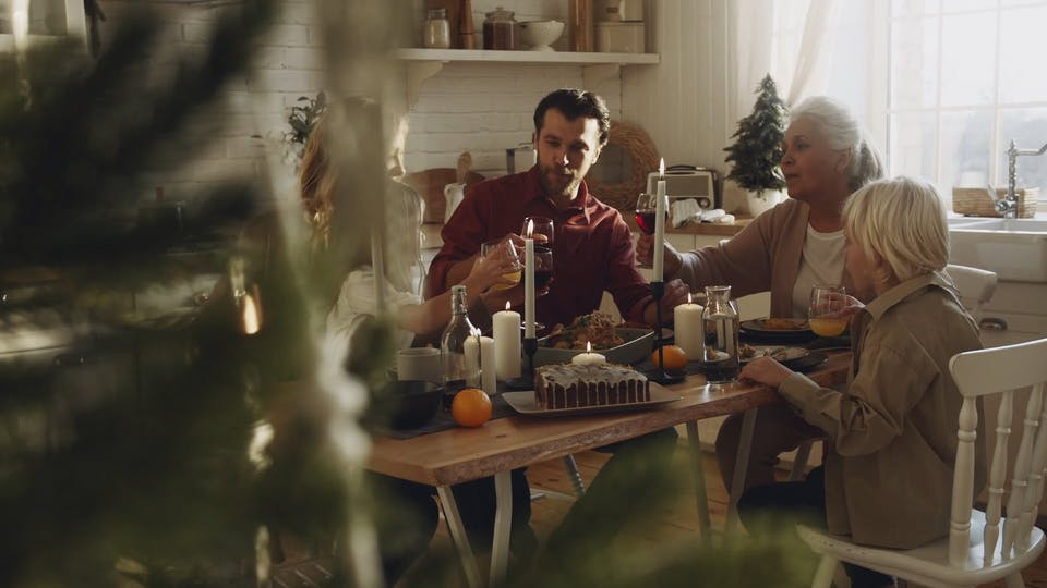 A Family Gathered Together In A Dining Table Tosses Their Glasses Of Drinks