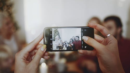 Taking A Photo Of A Family Using A Smart Cellphone