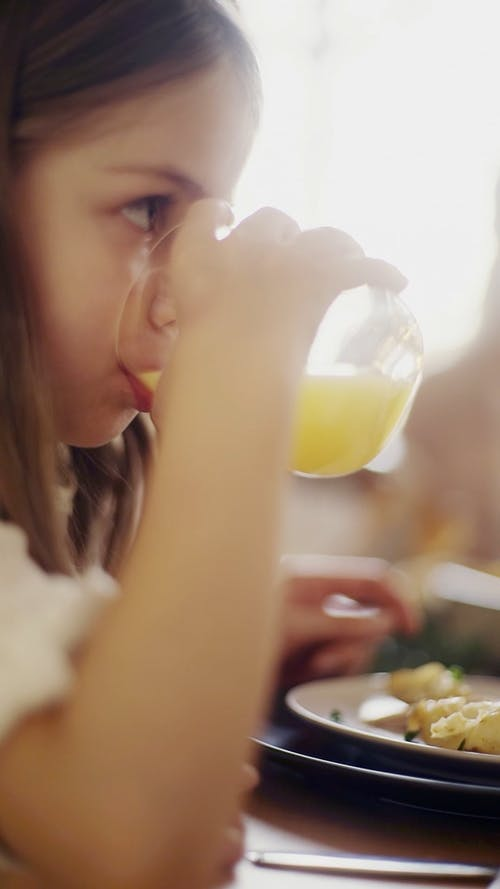 A Child Drinking A Juice From A Crystal Glass