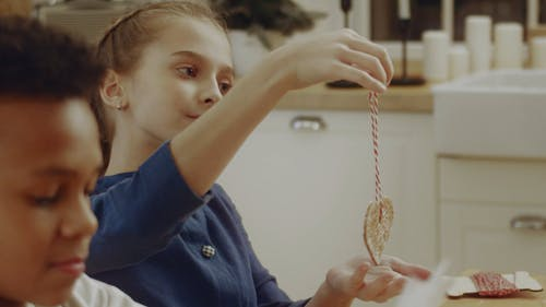 A Girl Showing A Cookie Hanging By A String