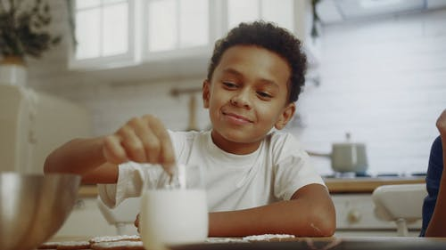 A Boy Dipping A Cookie He Decorated In A Glass Of Milk Before Eating Eat