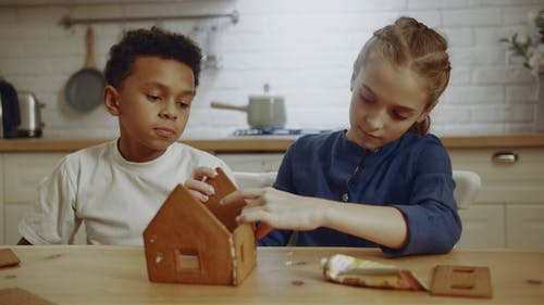 A Boy Watching a Girl Trying To Make A Model House Made Of Cookie