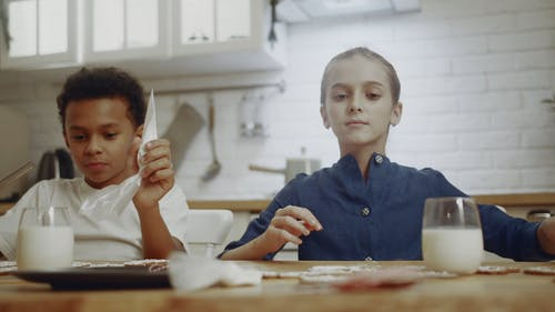 Kids In A Kitchen Doing Christmas Cookies Decoration