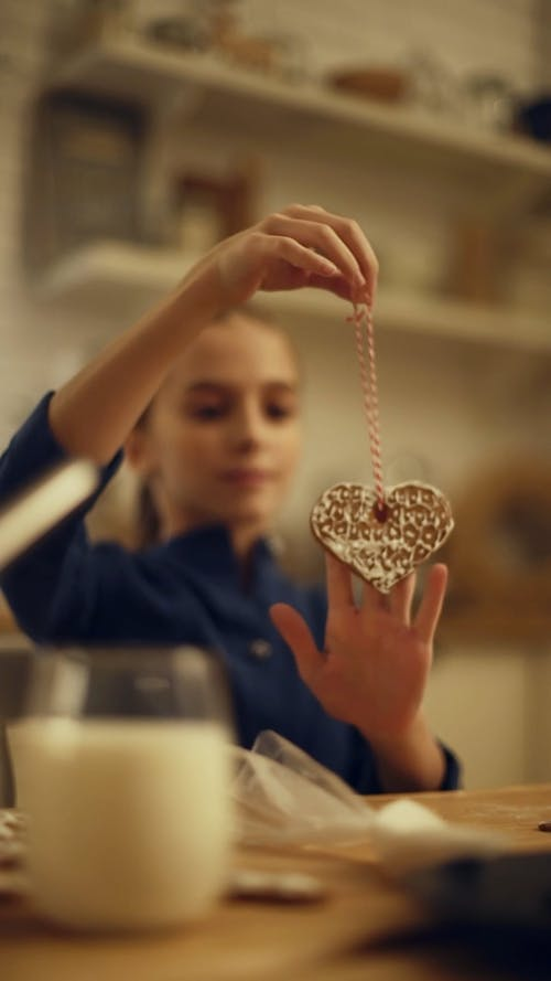 A Girl Showing A Cookie She Tied Into A String