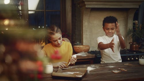 A Girl Putting Icing Decor On A Cookie While The Boy Beside Her Clapping Off Baking Powder On His Hand