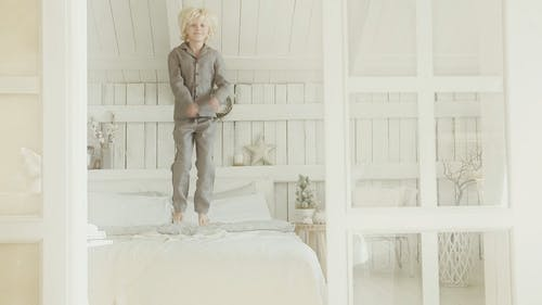 A Kid Wearing Pajama Jumping Up And Down On His Bed