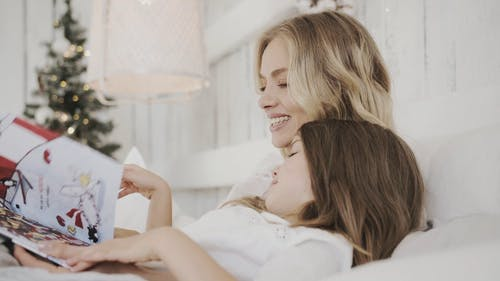 A Mother Embracing Her Daughter In Bed While Reading On A Children's Book
