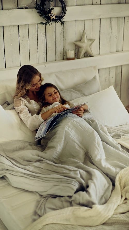 Mother And Daughter Together In A Bed Looking At A Magazine