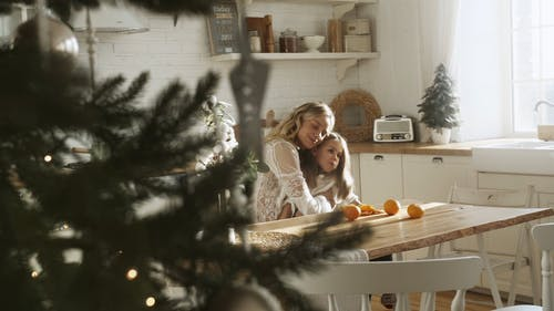Mother And Daughter Eating Orange Fruit In The Kitchen