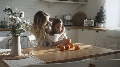 A Mother Fixes Her Daughter's Hair Who Is Peeling An Orange Fruit